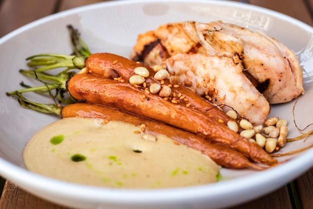 Pyszne danie ze smażonego kurczaka i duszonej marchewki z orzeszkami pinii. kremowy sos