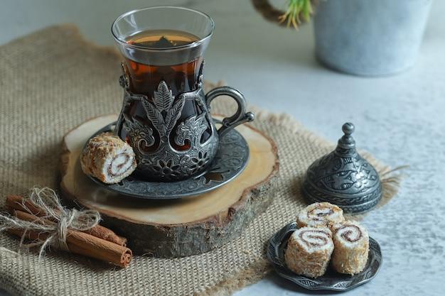 Pyszne desery lokum i szklanka herbaty na kamiennej powierzchni.