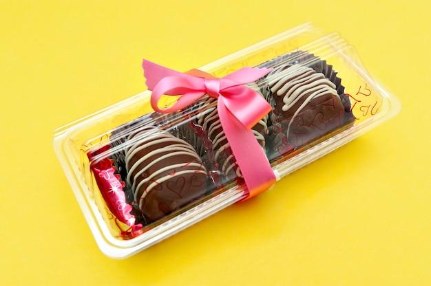 Pyszne domowe bonbon czekoladowe pakowane na prezent z czerwoną wstążką pojedynczo na żółtej powierzchni kopiowanie miejsca