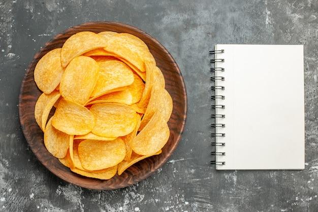 Pyszne domowe chipsy ziemniaczane na brązowym talerzu i notebooka na szarym stole