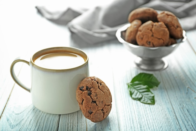 Pyszne domowe ciasteczka i filiżanka kawy na drewnianym stole