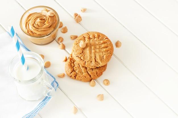 Pyszne domowe ciasteczka z masłem orzechowym z kubkiem mleka. biała drewniana przestrzeń. zdrowa przekąska lub smaczne śniadanie koncepcja.