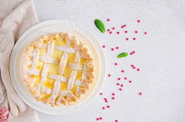 Pyszne domowe ciasto francuskie lub ciasto z nadzieniem serowym i wiśniami na białym talerzu na jasnej kamiennej ścianie.