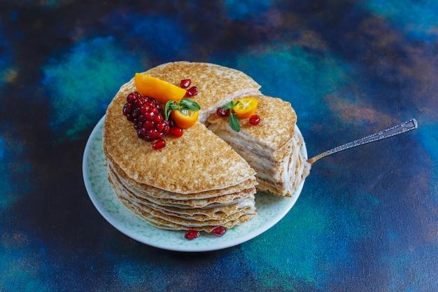 Pyszne domowe ciasto naleśnikowe ozdobione pestkami granatu i mandarynkami.