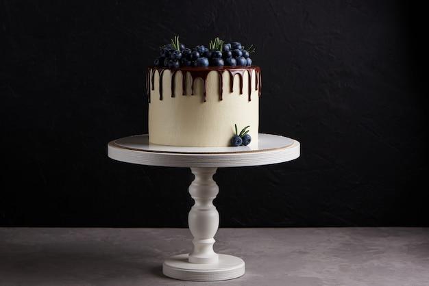 Pyszne domowe ciasto ozdobione świeżymi jagodami na białym drewnianym stojaku
