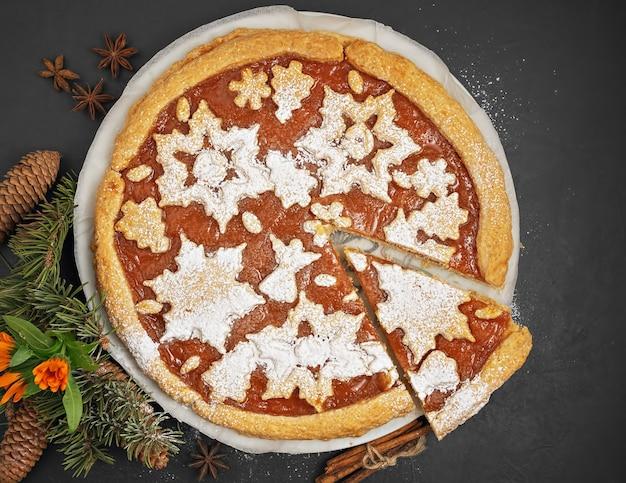 Pyszne domowe ciasto z dżemem persimmon. ciasto ozdobione jest świątecznymi postaciami z ciasteczek. obok ciasta są plastry persimmon i choinka. widok z góry.