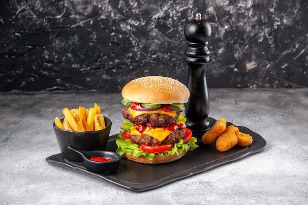 Pyszne domowe kanapki i frytki z keczupem widelcowym na czarnej desce na szarej izolowanej powierzchni