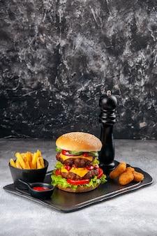 Pyszne domowe kanapki i frytki z ketchupem nuggetsy z kurczaka na czarnej desce na szarej trudnej powierzchni