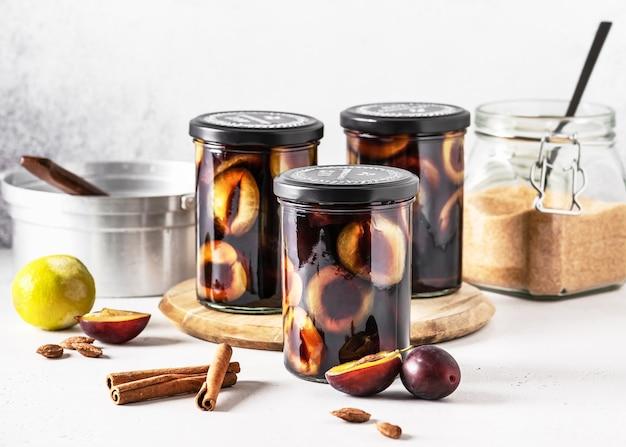 Pyszne domowe marynowane fioletowe śliwki z cynamonową limonką i brązowym cukrem w szklanych słojach