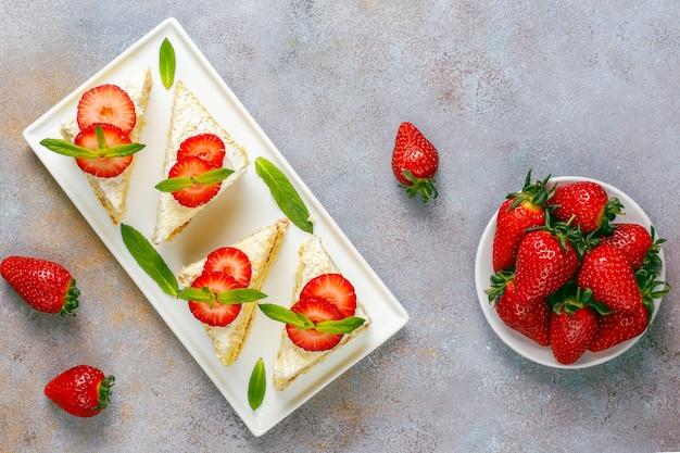 Pyszne domowe plastry ciasta truskawkowego ze śmietaną i świeżymi truskawkami