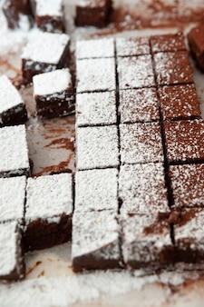 Pyszne domowe, surowe czekoladki pokrojone w kwadratowe kształty posypane cukrem pudrem