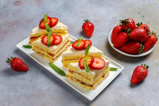 Pyszne domowe truskawki plastry ciasta ze śmietaną i świeże truskawki, widok z góry