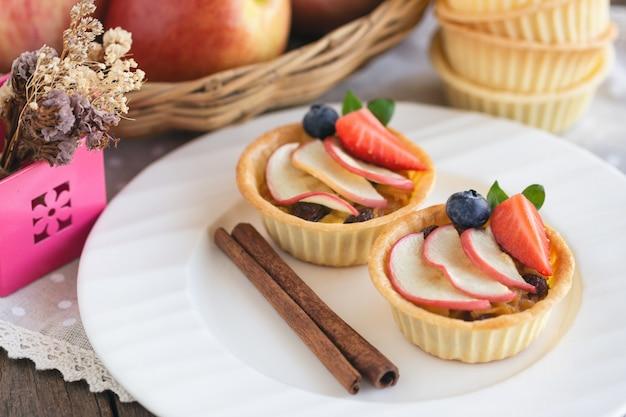 Pyszne domowej roboty tarta jabłkowa karmelowa ozdobiona plasterkami jabłka i truskawki.