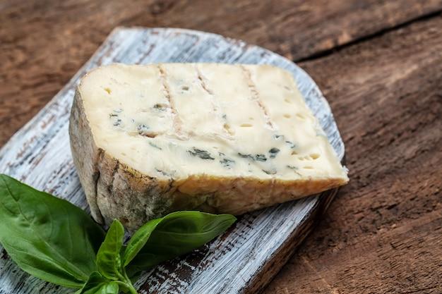 Pyszne dorblu ser pleśniowy, gorgonzola, roquefort na drewnianej desce. koncepcja zdrowej pożywienia. ścieśniać