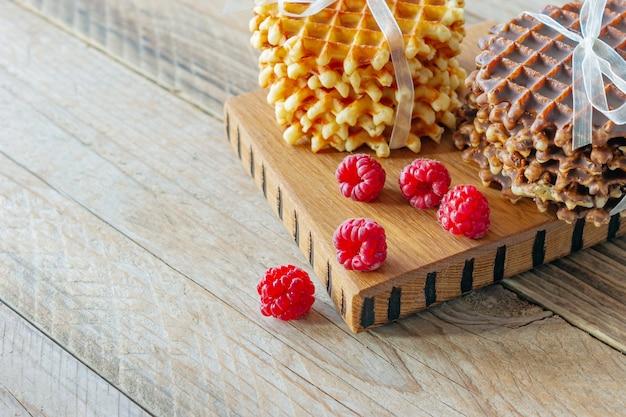 Pyszne gofry belgijskie z dodatkami malinowymi na drewnianej desce do krojenia. smaczne śniadanie.