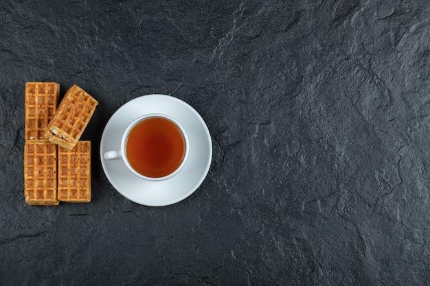 Pyszne gofry z filiżanką aromatycznej herbaty na ciemnej powierzchni.