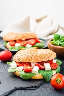 Pyszne gotowe do spożycia bajgle nadziewane pomidorami, fetą i liśćmi szpinaku na łupkowej desce na czarnym tle. lekka zdrowa przekąska. widok pionowy