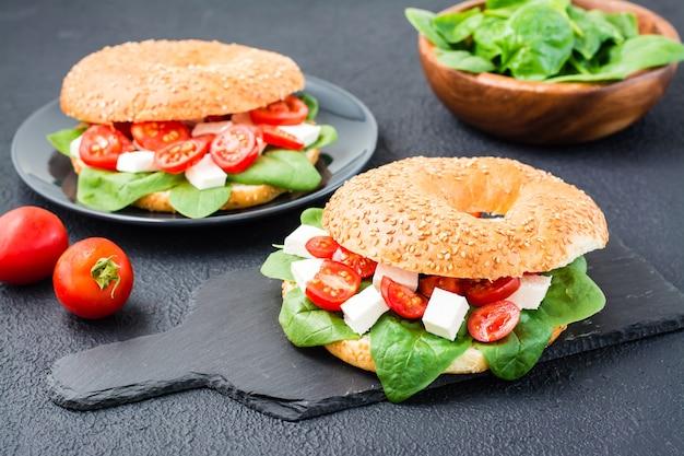 Pyszne gotowe do spożycia bajgle nadziewane pomidorami, fetą i liśćmi szpinaku na łupkowej desce na czarnym tle. lekka zdrowa przekąska