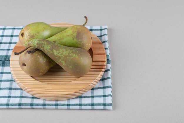 Pyszne gruszki zawinięte na drewnianym talerzu na ręczniku, na marmurze