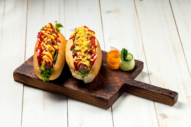 Pyszne hot dogi z keczupem i musztardą na białym tle