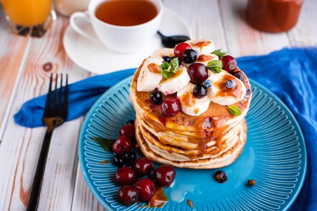 Pyszne i bujne naleśniki ze świeżymi owocami i jagodami, polane solonym karmelem. mięta, herbata, sok pomarańczowy, mleko na stole.