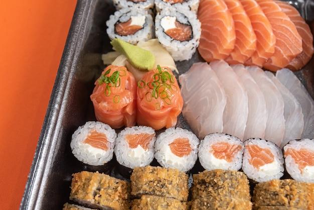 Pyszne i piękne sushi na pomarańczowym stole