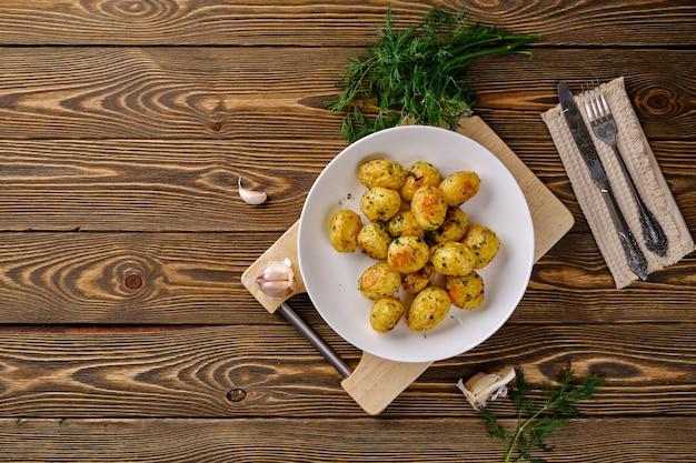 Pyszne i przydatne jedzenie. młode ziemniaki przekłuwane w piekarniku z pikantnymi ziołami i czosnkiem na starym rustykalnym stole