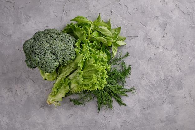 Pyszne i przydatne jedzenie. świeże i soczyste zielone warzywa na szarym tle z bliska