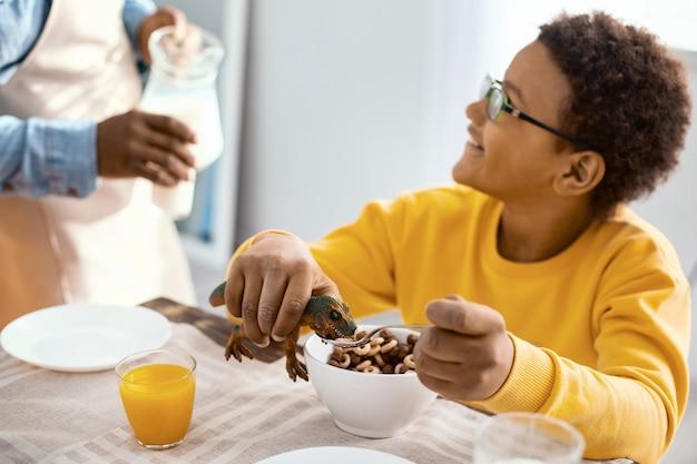 Pyszne i przyjemne. przyjemny chłopiec w wieku przedszkolnym, który uśmiecha się do swojego ojca i rozmawia z nim podczas jedzenia śniadania i karmienia swojego zabawkowego dinozaura płatkami zbożowymi