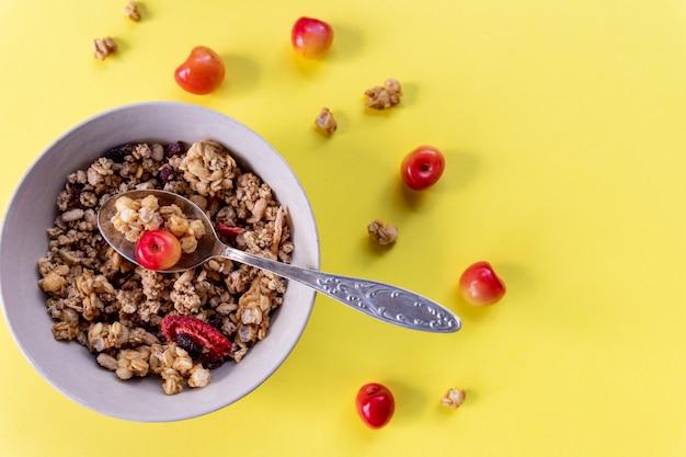 Pyszne i zdrowe pełnoziarniste śniadanie musli, z suszonymi owocami, orzechami, zbożami i świeżymi wiśniami