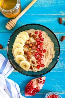 Pyszne i zdrowe płatki owsiane z bananem, pestkami granatu, migdałem i cynamonem. zdrowe śniadanie. żywność fitness. odpowiednie odżywianie. leżał płasko. widok z góry.