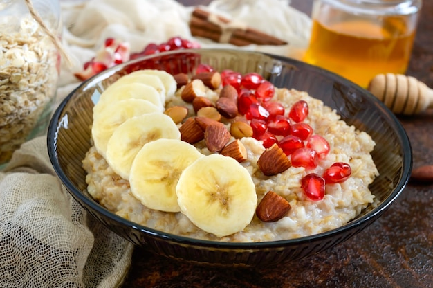 Pyszne i zdrowe płatki owsiane z bananem, pestkami granatu, migdałem i cynamonem. zdrowe śniadanie. żywność fitness. odpowiednie odżywianie.