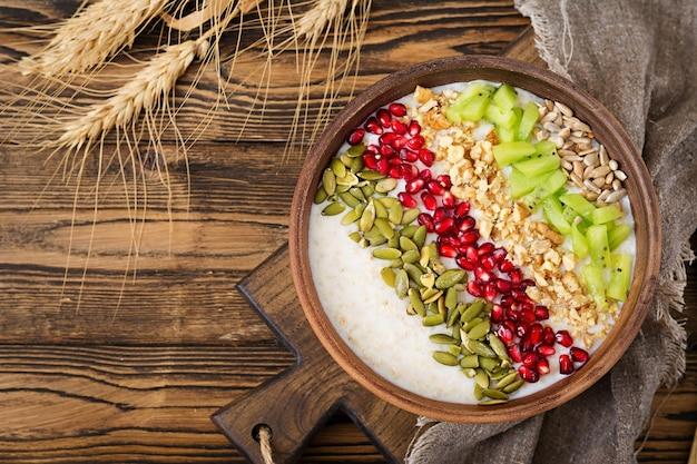 Pyszne i zdrowe płatki owsiane z kiwi, granatu i nasion. zdrowe śniadanie.