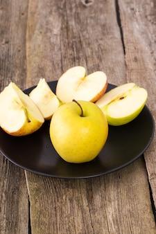 Pyszne jabłko na talerzu nad drewnianym stołem