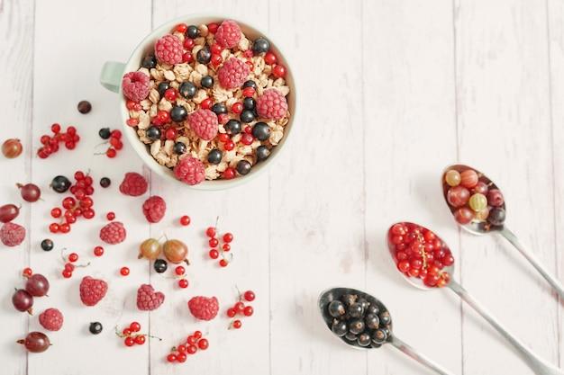 Pyszne jagody w białej filiżance i łyżkach