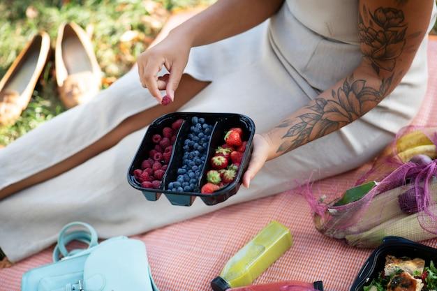 Pyszne jagody. widok z góry kobiety jedzącej pyszne jagody siedząc na trawie latem