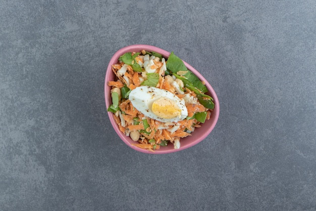 Pyszne jajka na twardo i świeża sałatka w różowej misce.