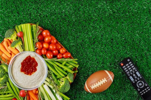 Pyszne jedzenie na imprezę z meczami futbolu amerykańskiego z pilotem do oglądania sportu na kanale telewizyjnym.
