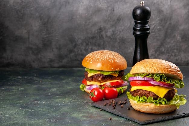 Pyszne kanapki z pieprzem na czarnej desce na ciemnej mieszance kolorowej powierzchni