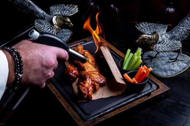 Pyszne kawałki skrzydełek z kurczaka grillowane płomieniami ognia. grillowanie i grillowanie. danie w restauracji