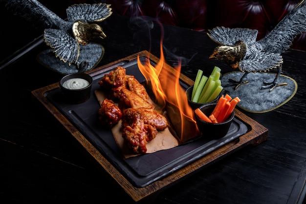 Pyszne kawałki skrzydełek z kurczaka grillowane płomieniami ognia. na restauracyjnym czarnym tle. grillowanie i grillowanie. danie w restauracji