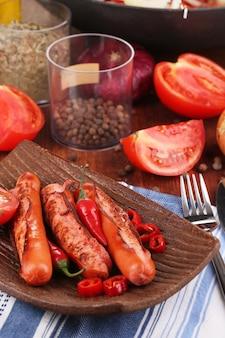 Pyszne kiełbaski z warzywami na talerzu na drewnianym stole z bliska