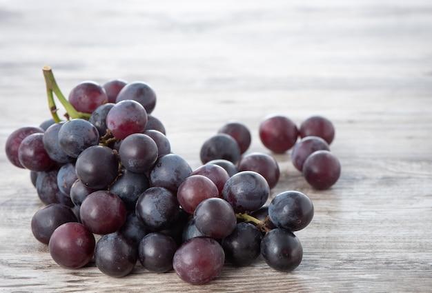 Pyszne kiść winogron owoców na talerzu na drewnianym stole