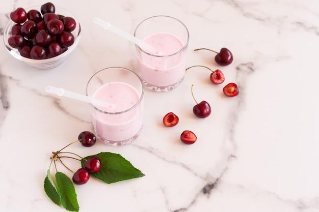 Pyszne koktajle wiśniowe w szklanych szklankach na marmurowym stole. miska ze świeżymi wiśniami.