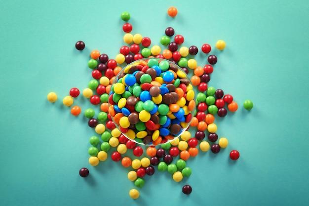 Pyszne kolorowe cukierki w misce na kolorowej powierzchni