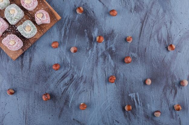 Pyszne kolorowe słodkie przysmaki z orzechami na desce.