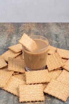 Pyszne krakersy z filiżanką kawy na tle marmuru. wysokiej jakości zdjęcie