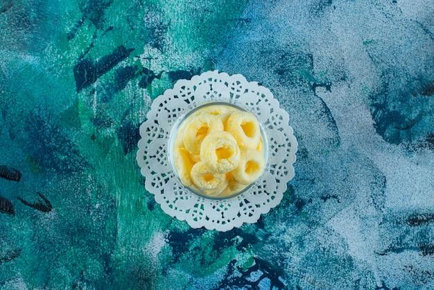 Pyszne krążki kukurydziane w misce na podstawce, na niebieskim stole.