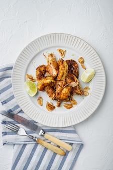 Pyszne krewetki pieczone z czosnkiem, sosem curry i mango, na talerzu, na białym tle