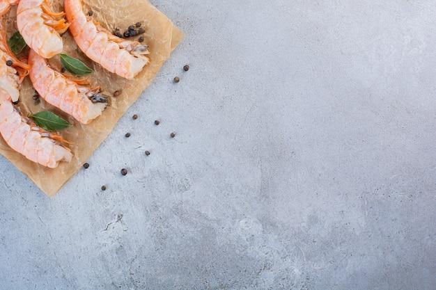 Pyszne krewetki z plasterkami cytryny i ziaren pieprzu na papierze do pieczenia